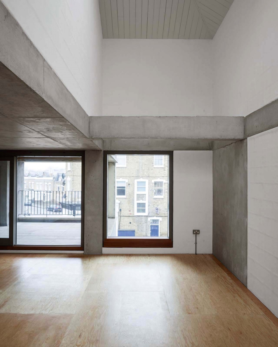 Four floors are bound together by two concrete columns that rise through the building and help to define the primary rectangular living space from which